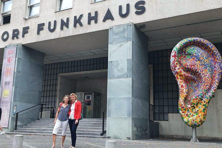 Zwei Frauen (eine dunkelhaarig, mit blauem Shirt und kurzer heller Hose; die andere blond, mit weißer Bluse, rotem Blazer und schwarzer Hose) stehen vor einem Gebäude mit der Aufschrift